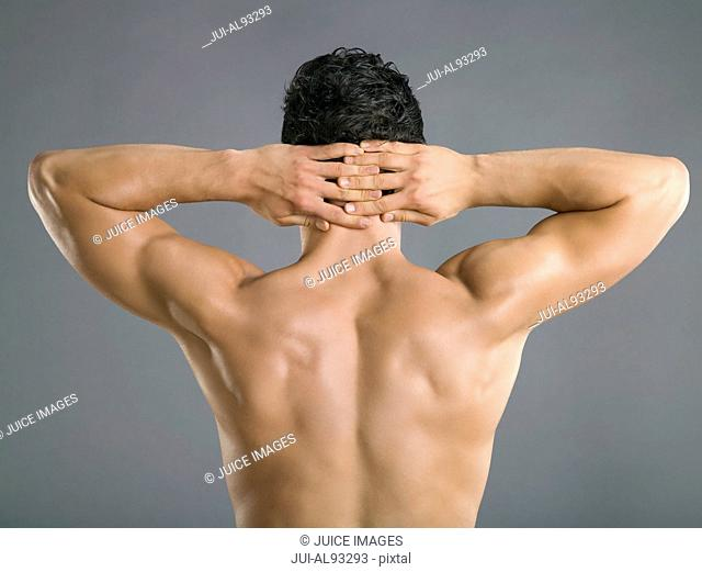 Rear view of man with hands clasped behind head