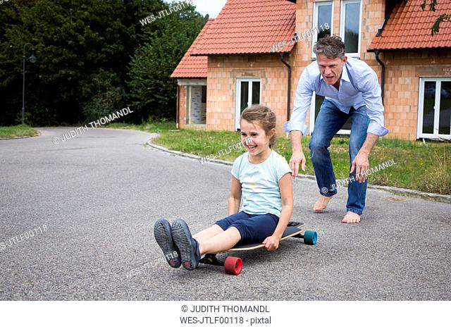 Father and daughter longboarding in garden