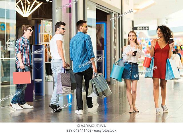 Sale in black Friday. The company of young people are engaged in shopping on a black Friday. Guys get acquainted with the girls in the mall