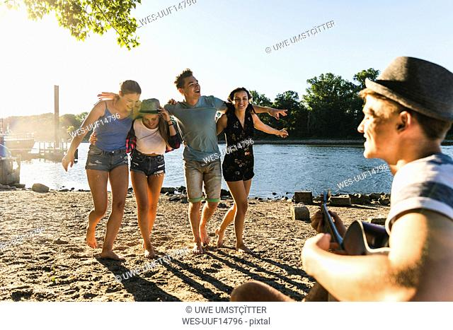 Group of friends having a party at the riverside