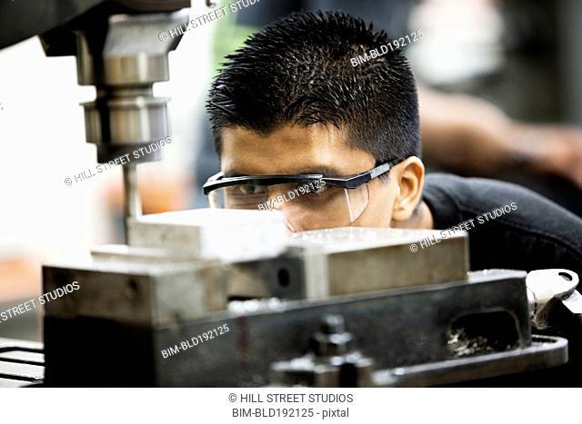 Hispanic man using machine in machine shop