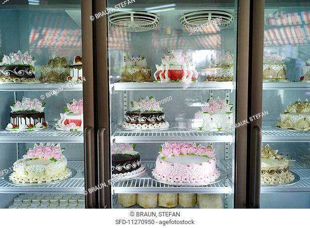 Various different celebratory cakes in a refrigerated display cabinet