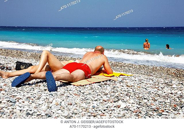 Young girls sunbathing at the beach , rhodes greece