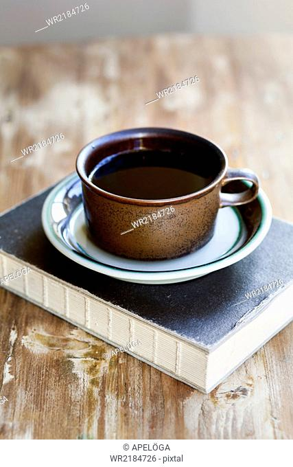 Black coffee and book on wooden table