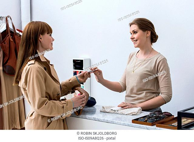 Woman making purchase in fashion shop
