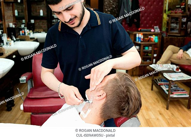 Young man in barbershop looking down shaving customer with straight razor