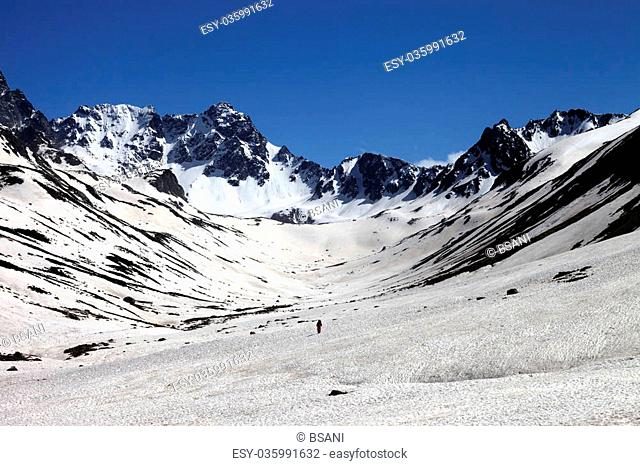 Hiker in snowy mountains at nice day. Turkey, Kachkar Mountains in spring (highest part of Pontic Mountains)