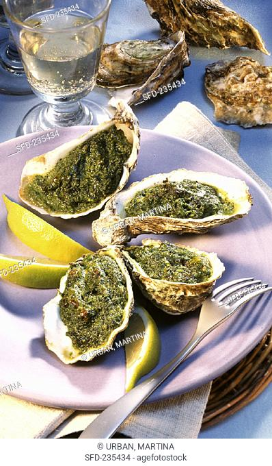 Baked oysters with lemon wedges, white wine