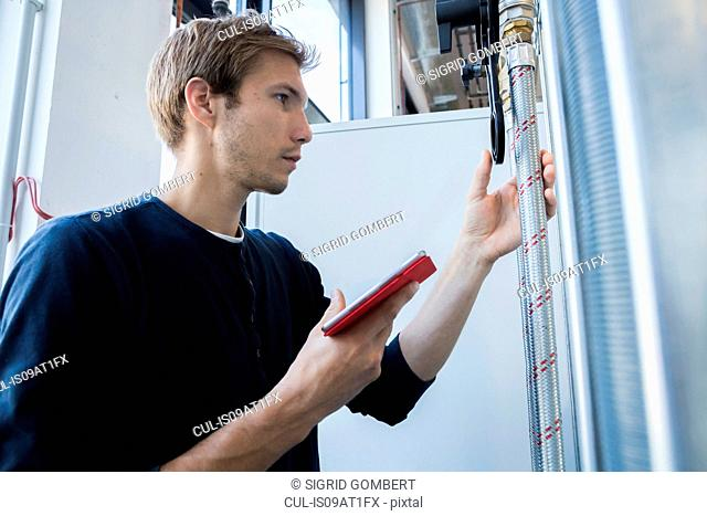 Factory technician using digital tablet to monitor pipes