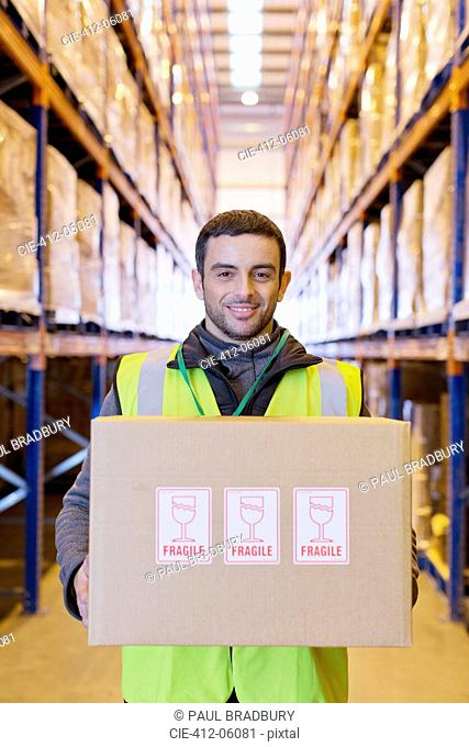 Worker carrying fragile box in warehouse