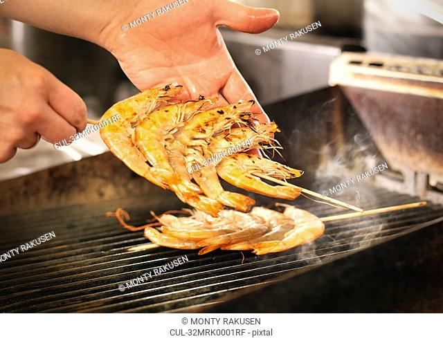 Chef cooking prawns on grill