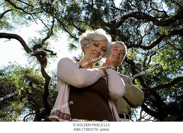 Mature couple posing under oak trees