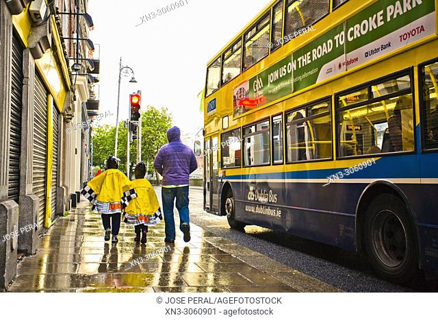 Rainy day, two children with raincoat walked by Dublin city, province of Leinster, Ireland, Europe