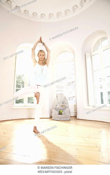 Woman holding a Vrksasana yoga pose in sunny studio