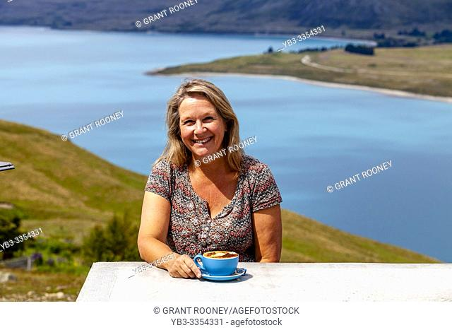 A Middle Aged Woman Sitting With A Cup Of Coffee Overlooking Lake Tekapo, Mt John Observatory Viewpoint, Mackenzie District, South Island, New Zealand