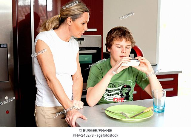 Teenager using a cell phone during meal