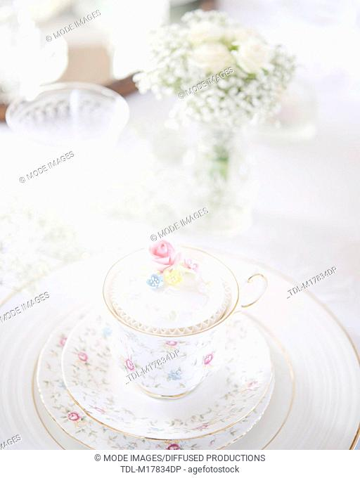 A wedding breakfast place setting, with china teacup, cupcake and vase of white flowers