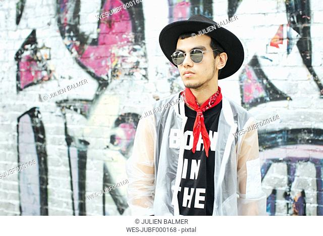Fashionable young man with hat and sunglasses wearing translucent rainjacket