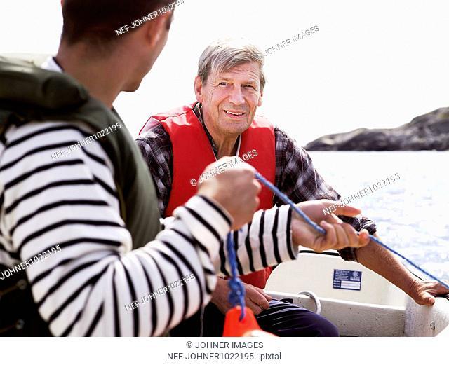 Sweden, Vastkusten, Marstrand, two men on boat