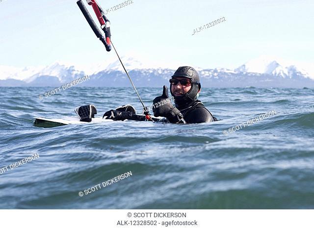 Man kitesurfing with Kenai Mountains in the background, Homer, South-central Alaska; Homer, Alaska, United States of America