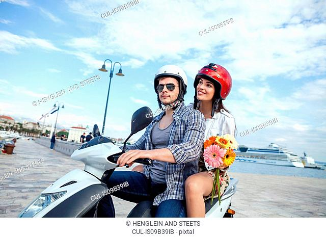 Young couple riding moped at harbour, Split, Dalmatia, Croatia