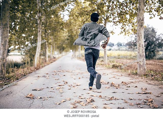 Spain, Tarragona, back view of young man running on autumnal country road