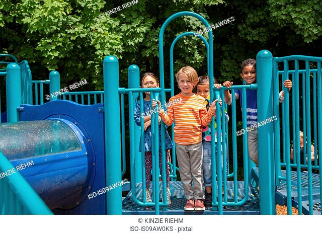 Portrait of four boys and girls on playground climbing frame