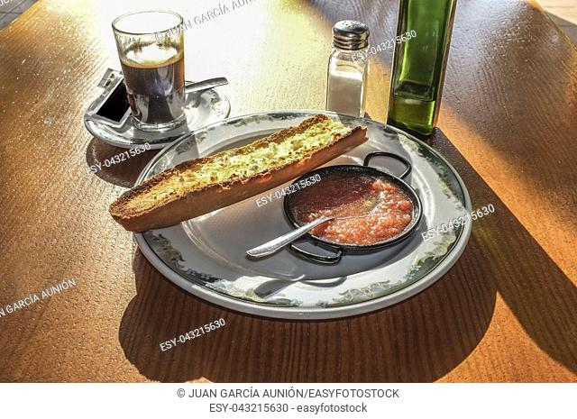Typical spanish breakfast, coffee and toast with olive oil and grinded natural tomato, Sunny table early in the morning