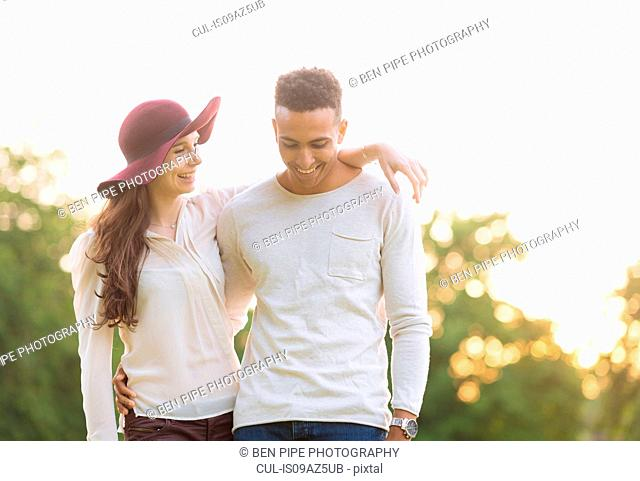 Young couple with arms around each other smiling