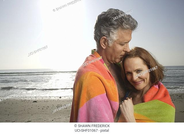 Mature couple kissing on the beach