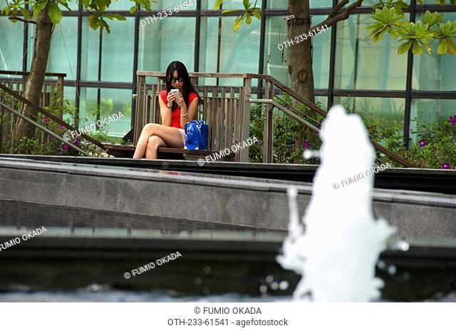 A woman at leisure, New Town Plaza terrace garden, Shatin, Hong Kong