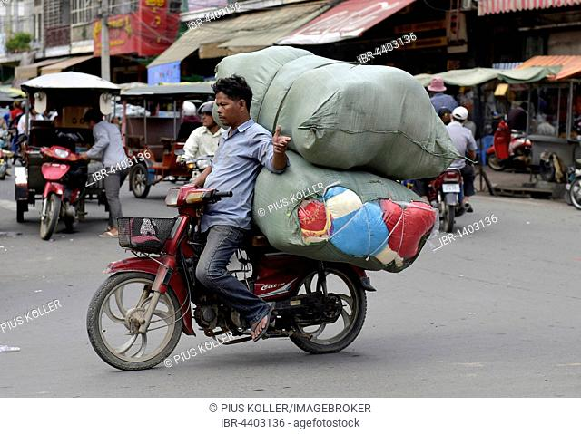 Man with moped and large sacks, Phnom Penh, Cambodia