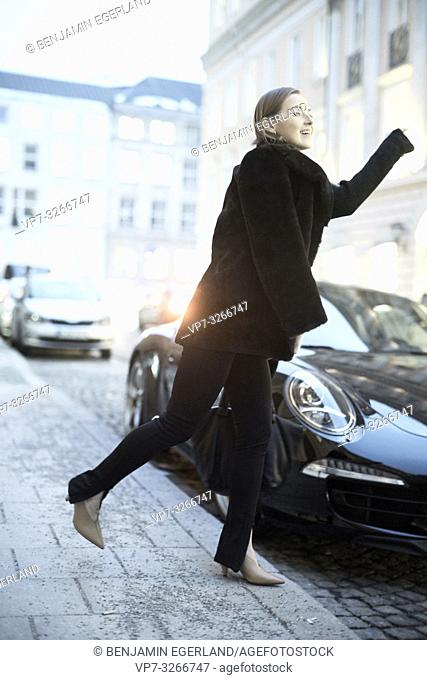 fashionable blogger woman walking at street in evening next to fancy car, in Munich, Germany