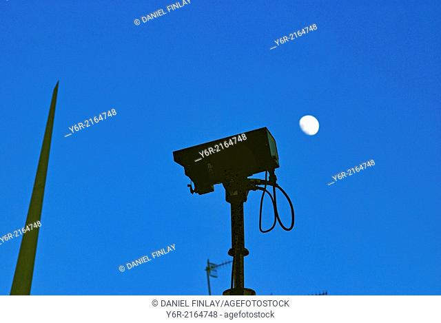 CCTV camera facing London Bridge and civic art in Southwark, London, England, at dusk, with the moon in the background