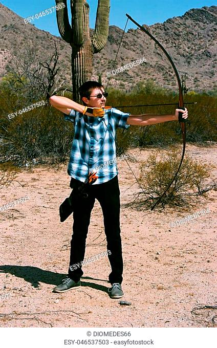 Young man shooting a long bow style bow and arrow in the desert