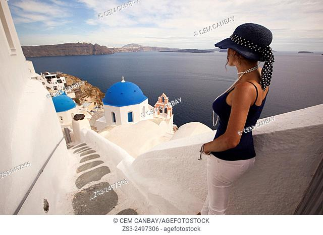 Woman in front of a blue domed church, Oia town, Santorini, Cyclades Islands, Greek Islands, Greece, Europe