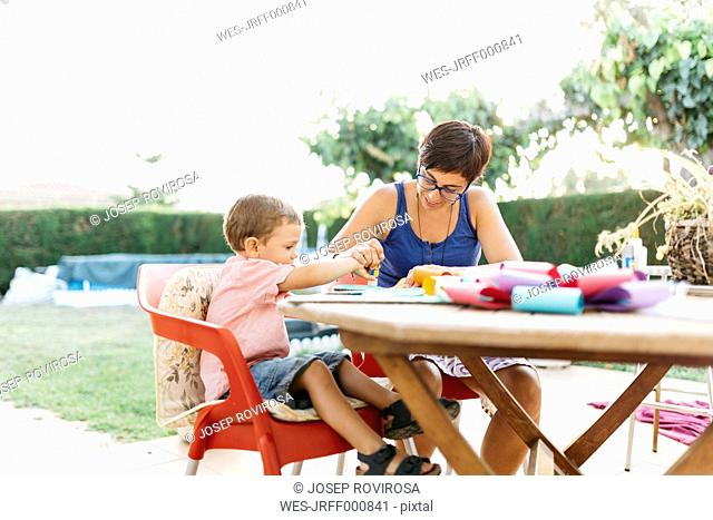 Mother and son doing handicrafts at garden table