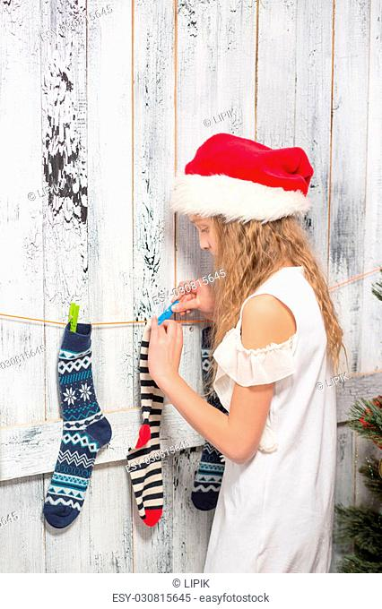 Teenage girl in Santa hat hanging New Year and Christmas socks for Santa Clause's presents or gifts