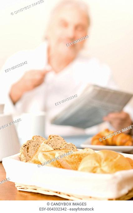Senior mature man - breakfast pastry and bread
