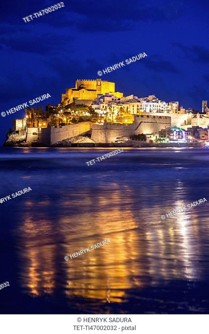 Spain, Valencian Community, Peniscola, Town with fortified wall by sea at dusk