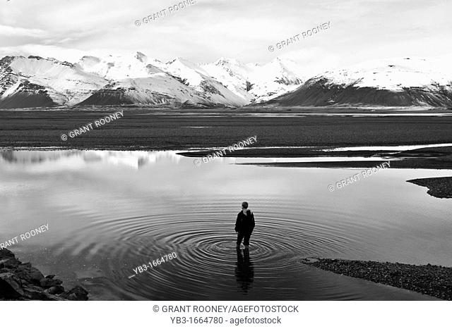 Boy standing in a Lake, near Hofn, Iceland