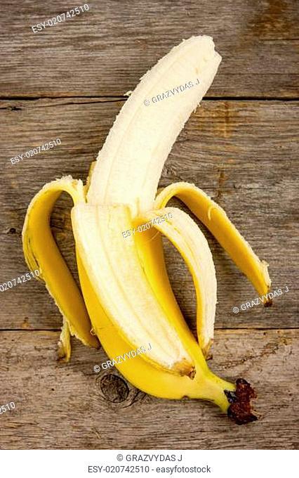 Peeled banana on the wood background