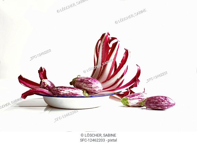 An arrangement of of trevisio and small aubergines on an old enamel plate