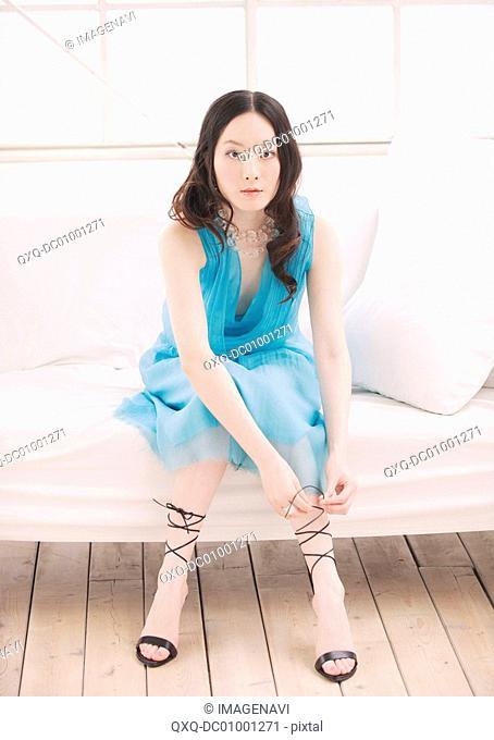 Woman in blue dress sitting on sofa
