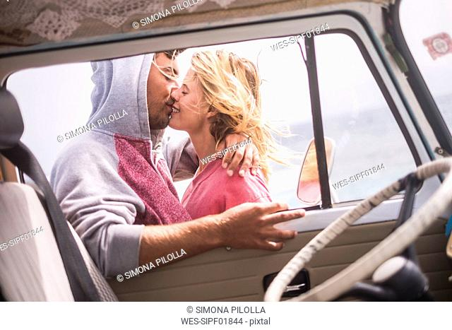 Spain, Tenerife, young couple in love on holidays with a van near the sea
