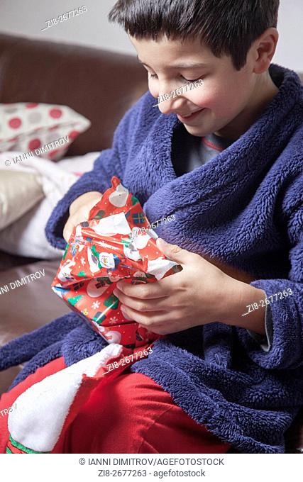 Happy child unwrapping Christmas presents