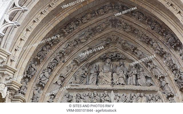 TILT down. CU. Daylight. Exterior: Carved Arch and Doors. The Portal of the Virgin. West facade. The Cathedral is in the High Gothic or Classical French style