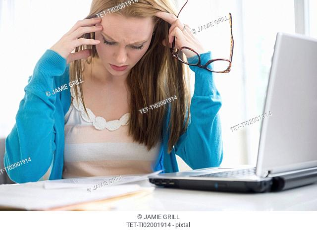 Frustrated young woman looking at bills