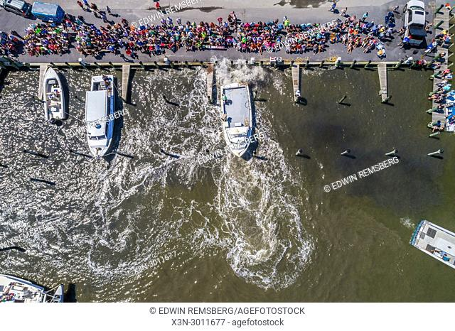 Looking directly down at spectators watching motor boats compete in docking contest. Deal Island, Maryland, USA