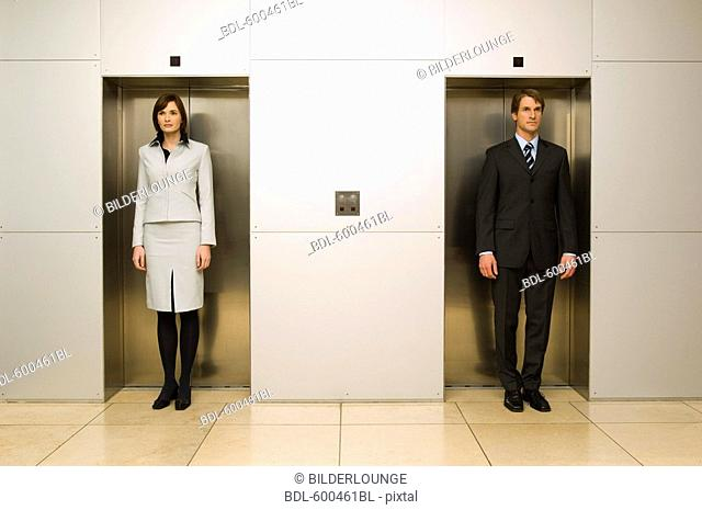 businesswoman standing side by side with male colleague in elevator doors